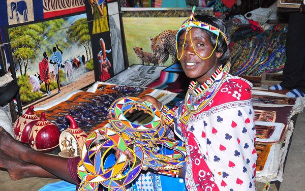 Colourfully clad vendor in the Maasai Market showing her wares